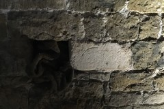 Below window, limestone block with overlaid circles.