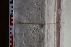 Cross, scribed semicircle, butterfly, dots/gouges, possible Marian, initials Mc,